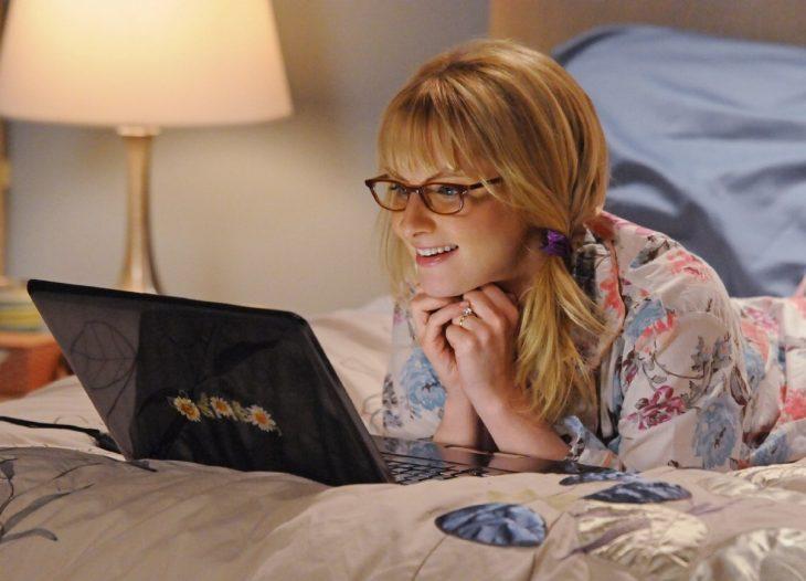 Chica recostada en la cama viendo su computadora