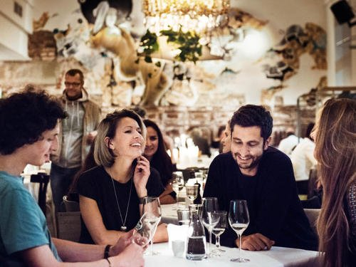 Grupo de chicos en un restaurante tomando una copa de vino