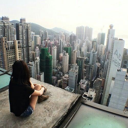 Chica sentada sobre un edificio observando la ciudad
