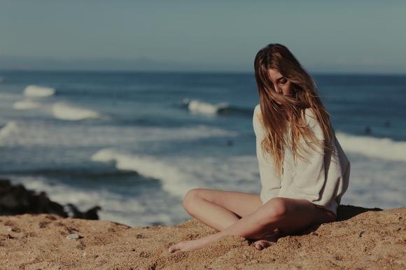 Chica sentada en la arena de la playa pensando