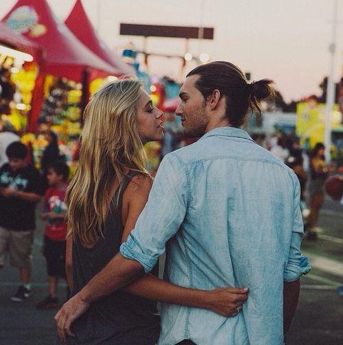 Chica abrazada a un chico que tiene el cabello largo mientras caminan por una feria