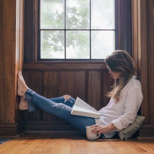 Chica sentada junto a la ventana leyendo un libro y tomando café
