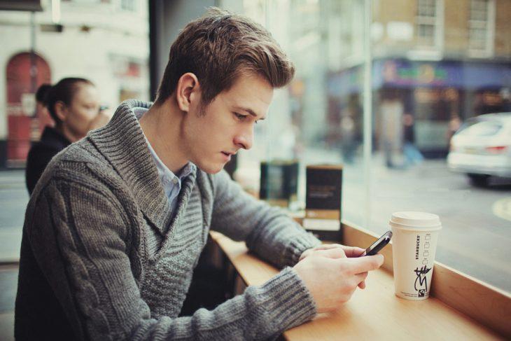 hombre en un café sentado en la barra mandando un mensaje con su celular