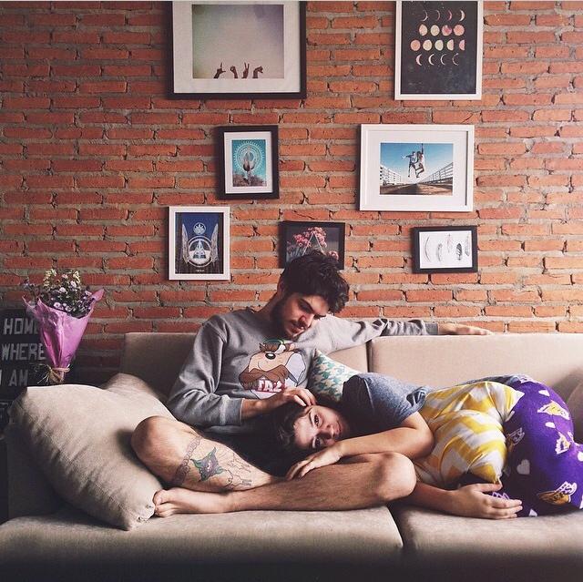 Chico y chica recostados en un sillon mientras él le masajea la cabeza