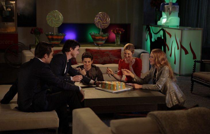 amigos sentados al rededor de un pastel celebrando