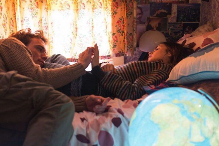 Pareja de novios recostados en la cama frente a una ventana conversando