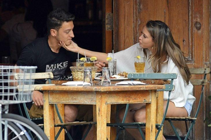 Pareja de novios en un restaurante comiendo y ella acariciándolo