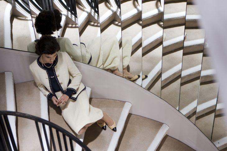 Escena de la película coco before chanel Audrey Tautou sentada en unas escaleras