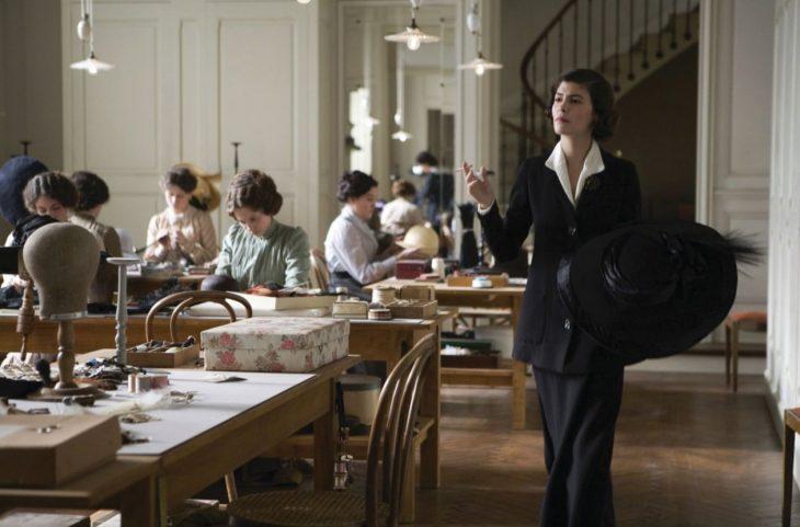 Escena de la película coco before chanel actriz audrey tatou caminando por una casa de costureras mientras fuma