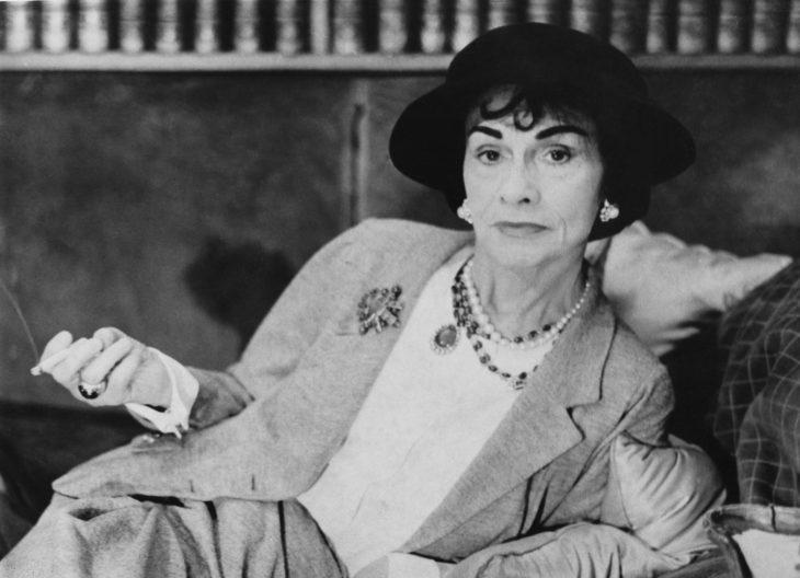 Diseñadora de modas Coco Chanel recostada sobre una cama fumando vistiendo un traje sastre y un sombrero