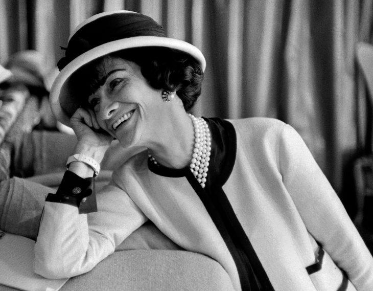 Diseñadora de modas coco chanel usando un traje sastre sombrero y perlas