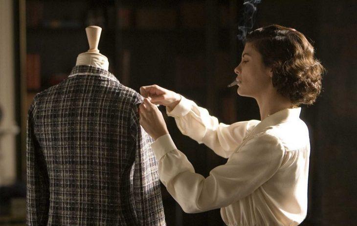 Audry tatou cociendo un vestido y fumando en la película before chanel