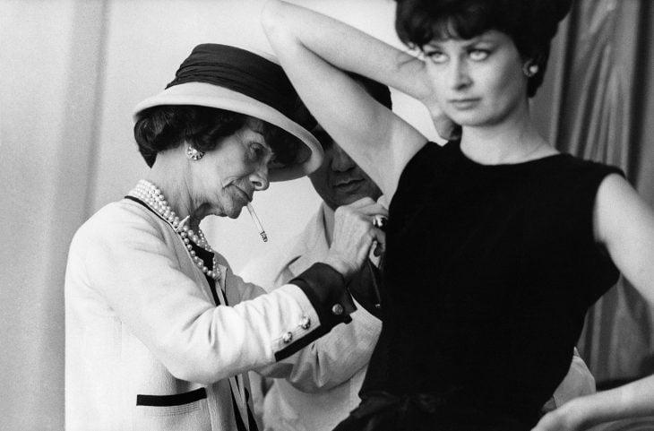 Diseñadora de modas coco chanel arreglando el vestido de una modelo mientras fuma