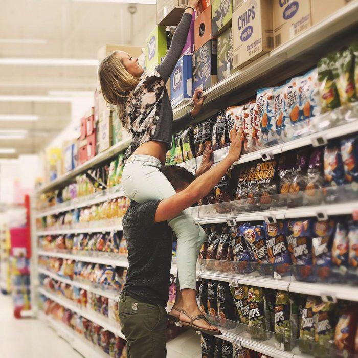 Chico ayudando a una chica a alcanzar productos de un estante