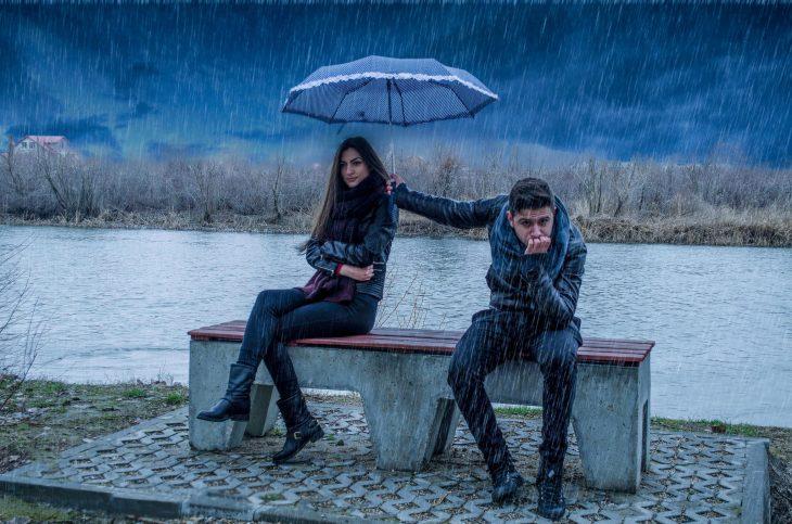 Chica enojada y su novio protegiéndola de la lluvia