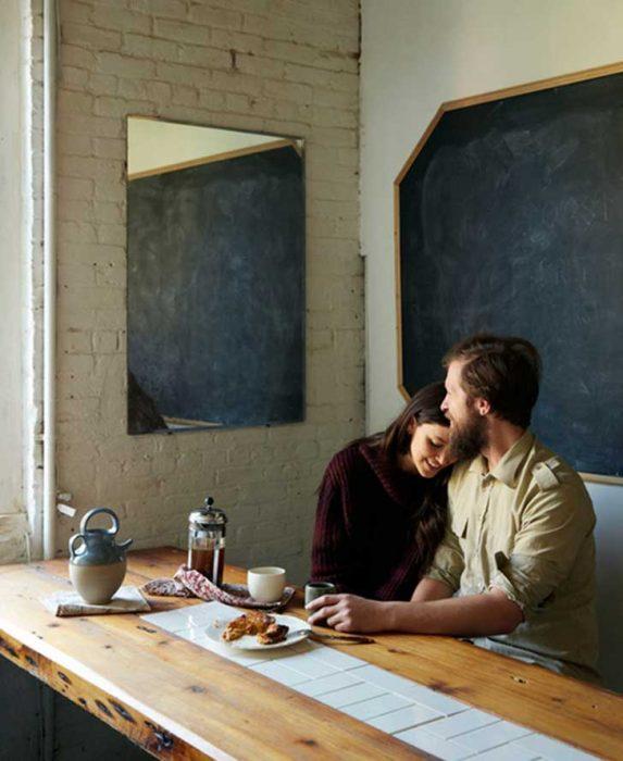 chico con barba abrazando a una chica mientras están en la mesa de la cocina comiendo