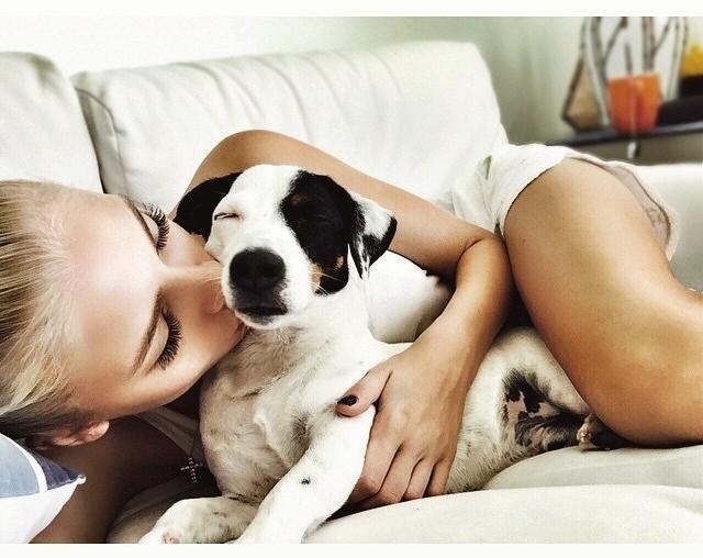Perro durmiendo en la cama con una chica