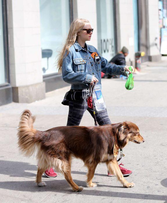 Chica levantando los desechos de un perro