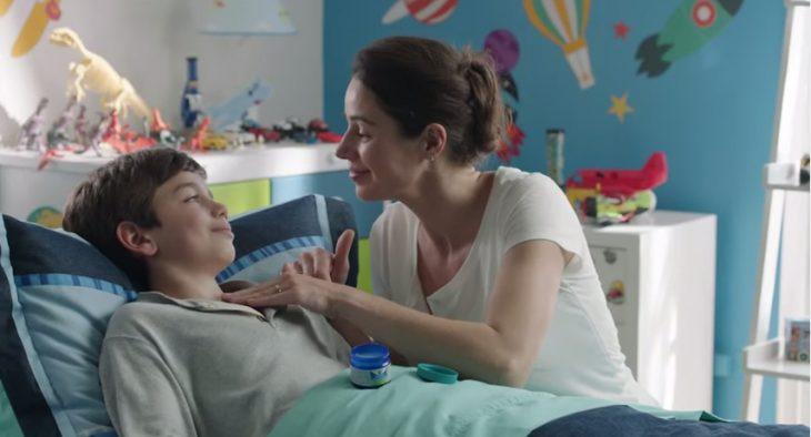 Mamá poniendo vick VapoRub en el pecho de un niño recostado en la cama