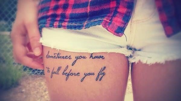 Chica con un short donde muestra su tatuaje con una frase