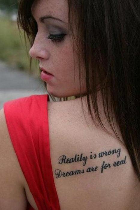 Chica vestida de rojo con un tatuaje de una frase en su espalda