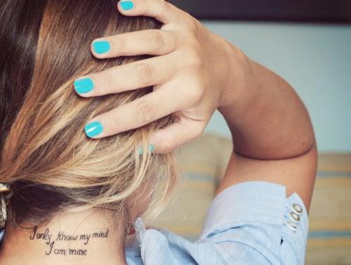 chica mostrando su tatuaje de una frase en la nuca