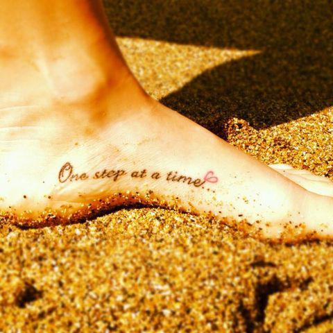 chica con un pie tatuado con una frase que esta sobre la arena