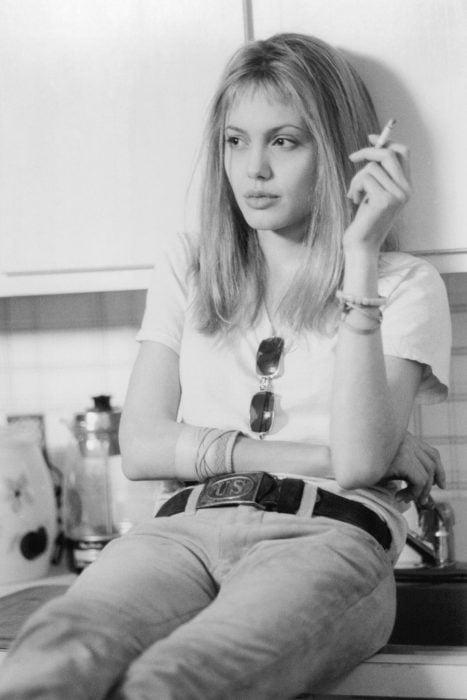 Angelina jolie en la película inocencia interrumpida fumando un cigarrillo mientras esta sentada en la barra de la cocina