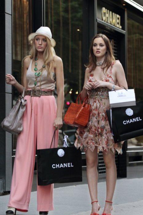 Chicas cargando bolsas de ropa afuera de una calle