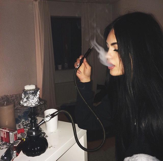 Chica fumando de una pipa