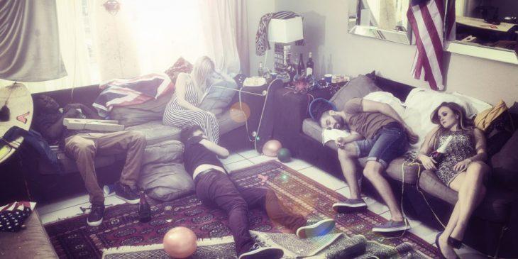 Chicos recostados en la sala de una casa después de una fiesta