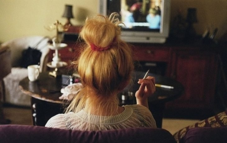 Chica de espaldas observando televisión basura