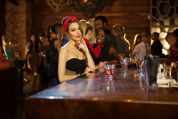Chica sentada en la barra de un bar tomando una bebida