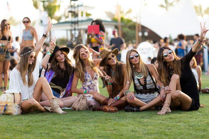 Chicas sentadas en el pasto en el festival de coachella 2015