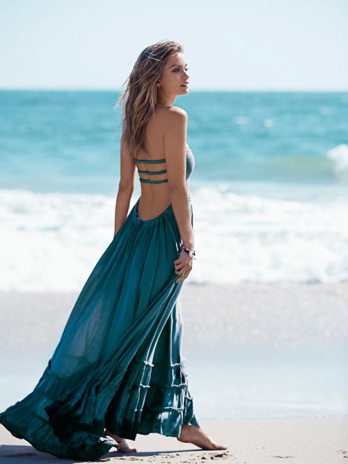 Chica con un vestido azul caminando por la playa