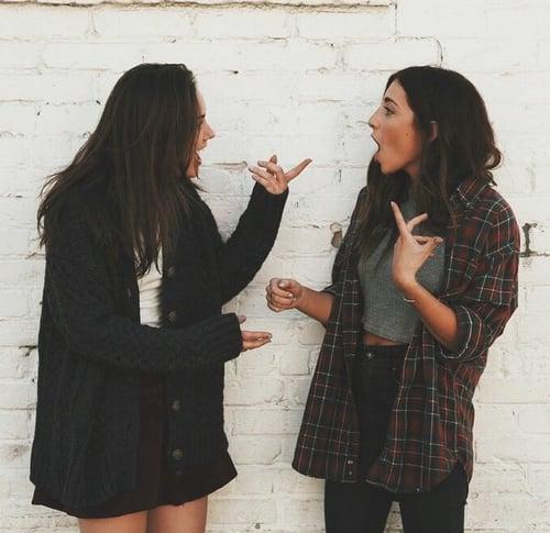 Chicas hablando mientras están recargadas en una pared
