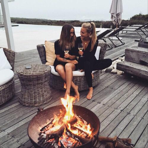 Chicas sentadas frente a una fogata conversando