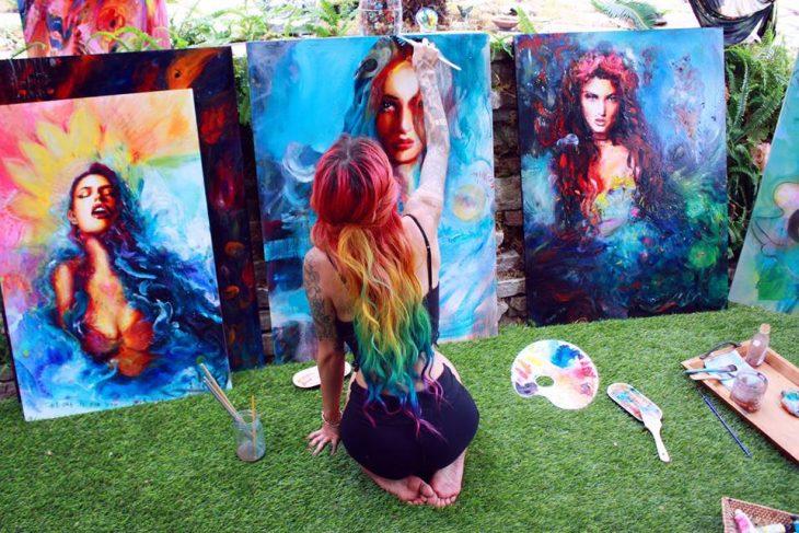 Chica de espaldas pintando un cuadro de una mujer