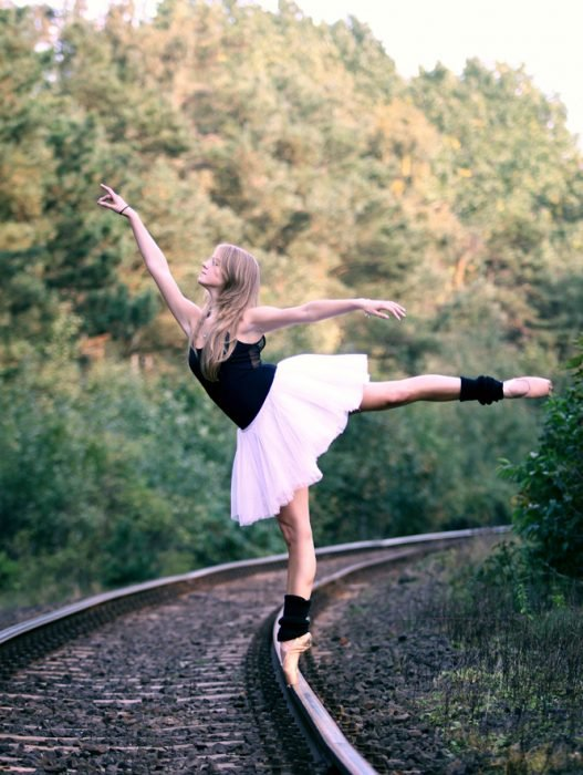 bailarina de ballet parada en puntas sobre las vías del tren