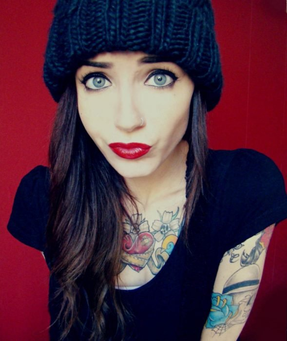 Chica labios rojos y tatuajes en el cuerpo