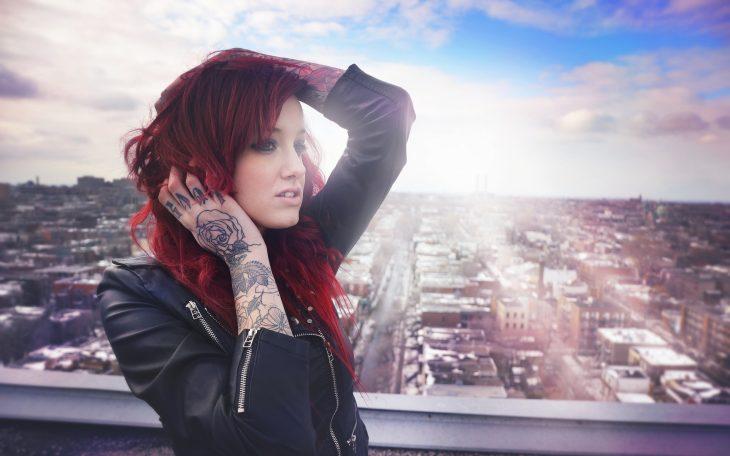 Chica con chamarra de piel y tatuajes en los brazos
