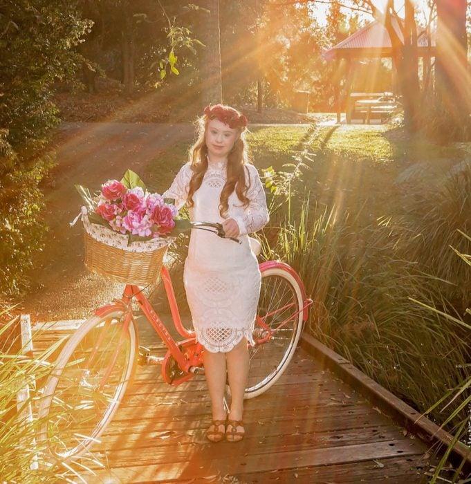 Niña con síndrome de down al lado de una bicicleta