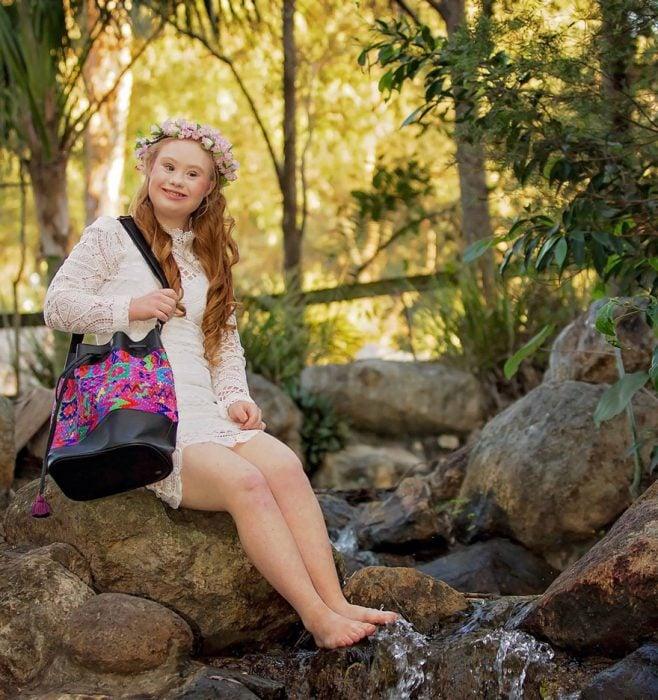 Chica con síndrome de down sentada en las rocas posando para una fotografía
