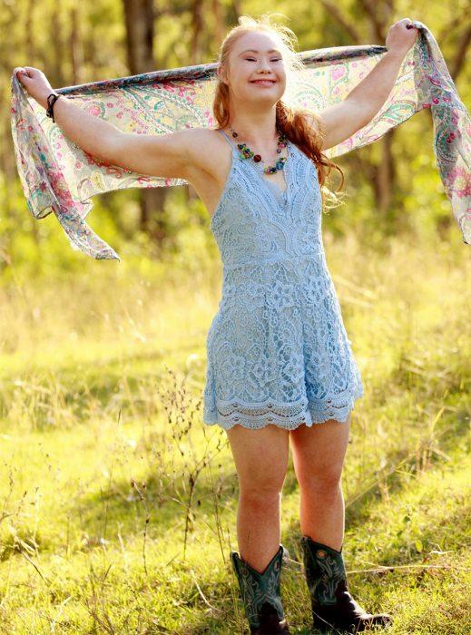 Niña con síndrome de down usando un vestido azul y botas alzando una mascada con sus manos