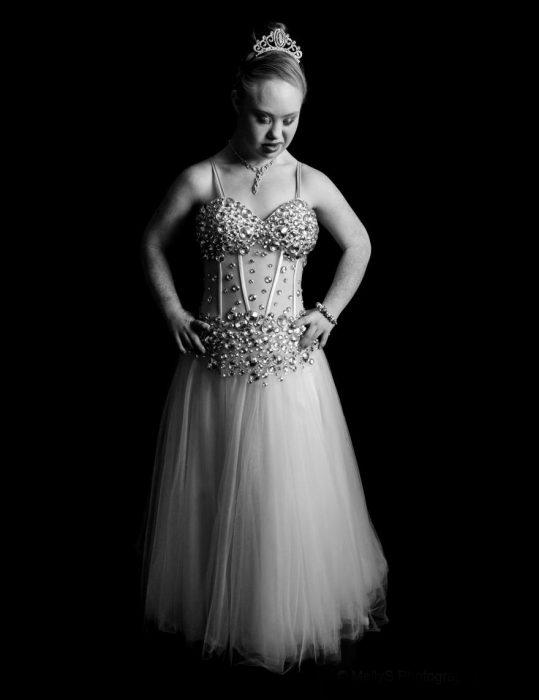 niña modelo con síndrome de down usando un vestido con piedras posando para una foto