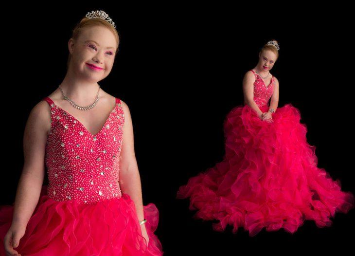 Chica con síndrome de down usando un vestido de quinciañera posando para una foto