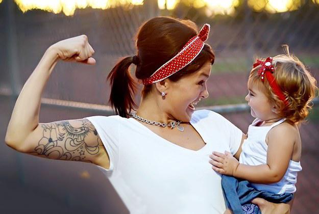 Madre sosteniendo a su hija en brazos mientras levanta su puño sobre ella