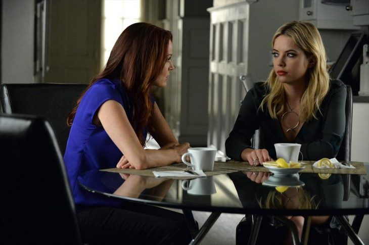 LAURA LEIGHTON, ASHLEY BENSON de la serie pretty little liars conversando sentadas en la mesa