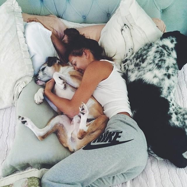 Chica acostada en su cama con dos perros