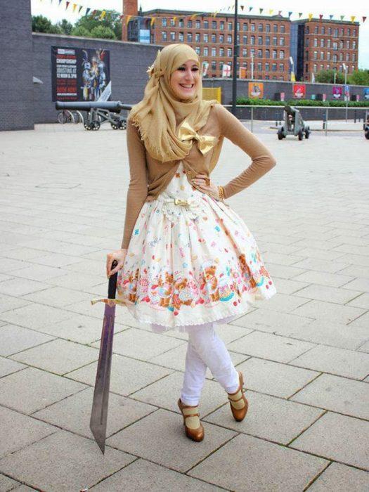Chica usando un vestido blanco con flores amarillas, mayas y zapatos de color dorado como su suéter y su hijab